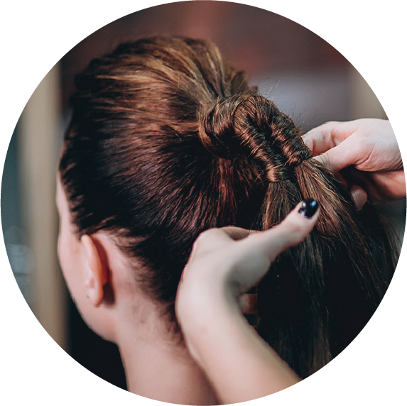 An image of a women getting her hair tied in a ponytail